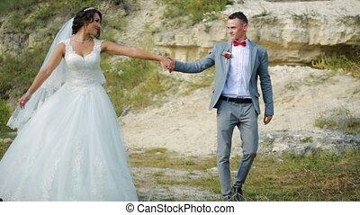 Happy couple walk near high sandstone cliffs. Honeymoon...