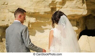 Happy couple walk near high sandstone cliffs