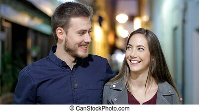 Happy couple walking and talking in the night