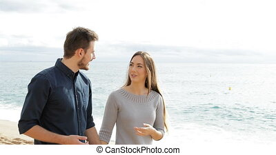 Happy couple walking and talking on the beach
