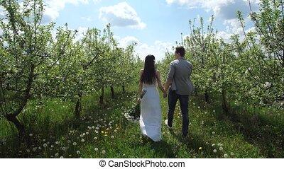Happy couple walking hand in hand among trees