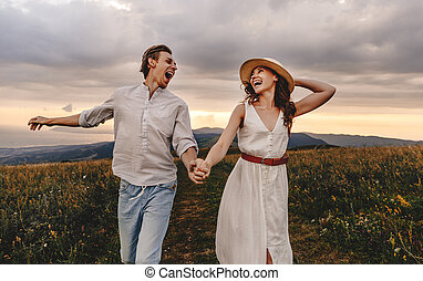 happy couple walking in nature at sunset