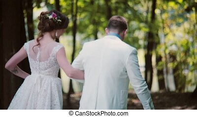 Happy couple walking in park on their wedding day. Back view of beautiful bride and groom, holding hands. Steadicam shot
