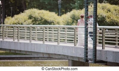 Happy couple walking on a bridge on wedding day. Back view of beautiful bride and groom, holding hands. Steadicam shot