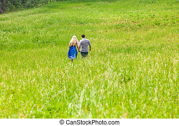 Happy couple walking on a meadow in summer nature, rear view