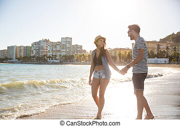 Happy couple walking on coast holding hands