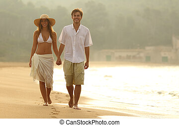 Happy couple walking on the beach at sunset