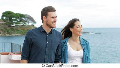 Happy couple walking on the beach pointing horizon