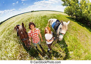 Happy couple walking with their purebred horses