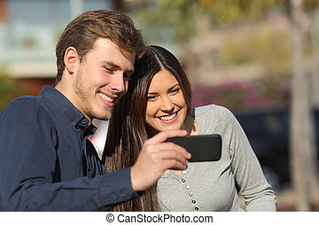Happy couple watching media in a smart phone outdoors