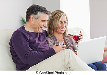 Happy couple watching their laptop and drinking wine