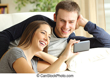 Happy couple watching videos in a phone - Happy couple...