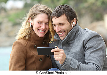 Happy couple watching videos sharing earbuds