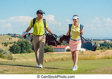 Happy couple wearing golf outfits and carrying stand bags