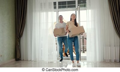 couple wearing jeans enters new house glass panoramic door