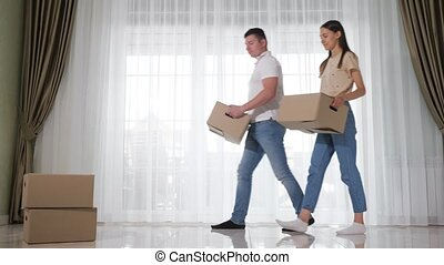 happy couple wearing jeans enters new house holding big boxes