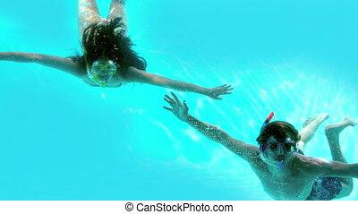 Happy couple wearing snorkels under