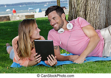 happy couple with a tablet lay on the ground