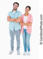 Happy couple with arms crossed on white background