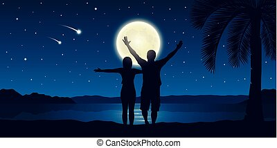 happy couple with arms raised enjoy the full moon and falling stars on the beach