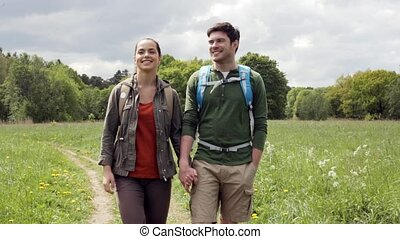 happy couple with backpacks hiking outdoors 4