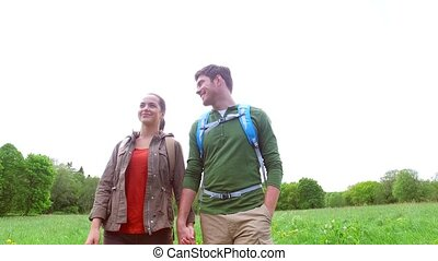happy couple with backpacks walk on country road 1