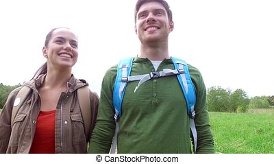 happy couple with backpacks walk on country road 2