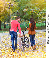 Happy couple with bicycle in autumn park