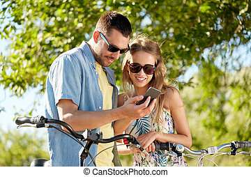 happy couple with bicycles and smartphone outdoors - people,...