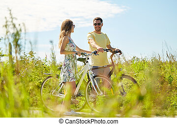 happy couple with bicycles at country - people, leisure and...