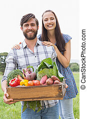 Happy couple with box of veg on a sunny day