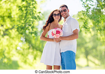 happy couple with bunch of flowers hugging