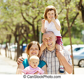 Happy couple  with children in summer
