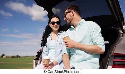 happy couple with coffee at hatchback car trunk 39