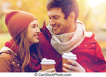 happy couple with coffee walking in autumn park - love,...