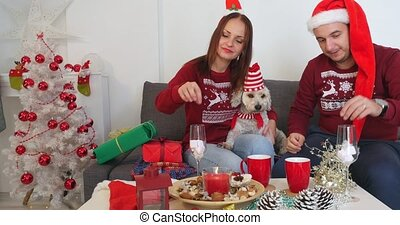 Happy couple with dog, all in Christmas clothes sitting near Christmas tree