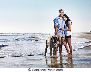 happy couple with dog on beach
