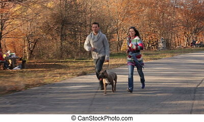 Happy Couple With Dog Running In Autumn Park