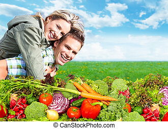 Happy couple with fresh vegetables and fruits.