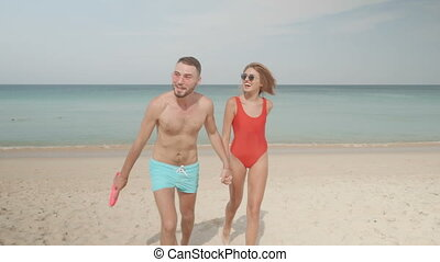 Happy couple with frisbee on the beach