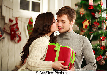 Happy couple with gift at home on a background of the Christmas tree