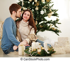 Happy couple with gifts on a background of Christmas tree at home