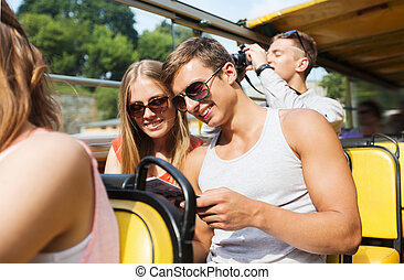 happy couple with guidebook traveling by tour bus