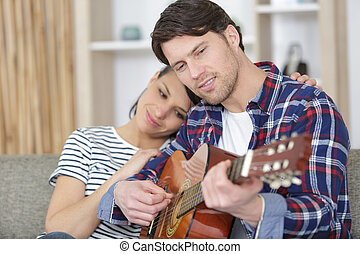 happy couple with guitar sitting on couch at home