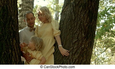 Happy couple with her little daughter kissing over a forest background