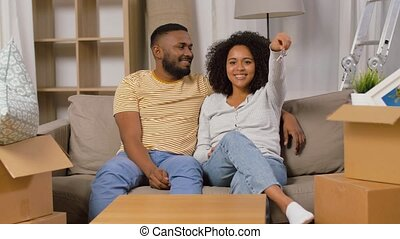 mortgage, eco living and real estate concept - happy african american couple with house key and boxes moving to new home and kissing