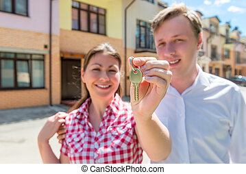 happy couple with keys to a new home. focus on the key