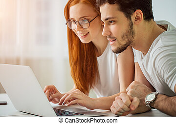 couple with laptop spending time together at home