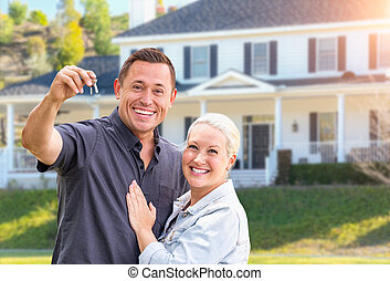 Happy Couple With New House Keys In Front Beautiful House