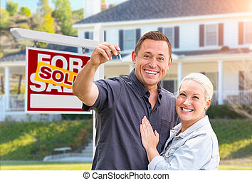 Happy Couple With New House Keys In Front of Sold Real Estate Sign and Beautiful House